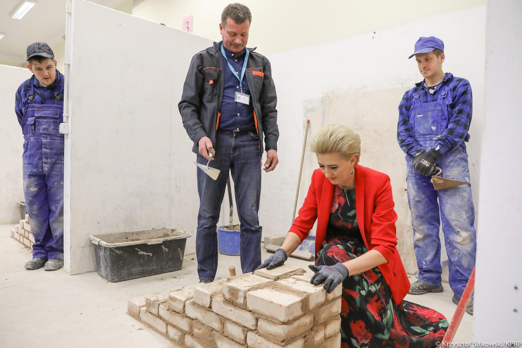 Agata Duda układa cegły